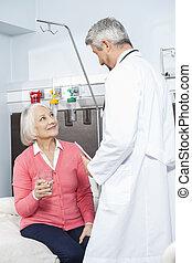 senior, patiënt, vasthouden, waterglas, terwijl, kijken naar, arts