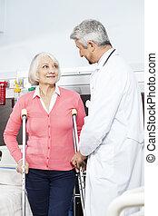 senior, patiënt, wezen, geassisteerd, door, arts, met, krukken