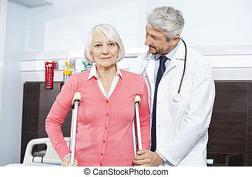 senior, patiënt, wezen, geassisteerd, door, mondige arts, met, krukken