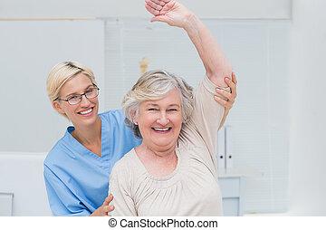 senior, patiënt, wezen, geassisteerd, door, verpleegkundige, in, het opheffen van wapen