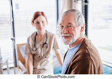 Senior patient and doctor sitting on bed in hospital, looking at camera.
