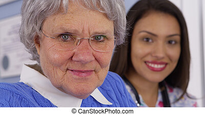 Senior patient and Mexican caregiver looking at camera
