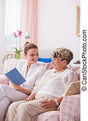 Senior patient and nurse with book