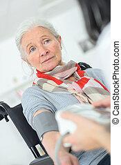 Senior patient blood pressure check