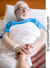 senior patient holding hands