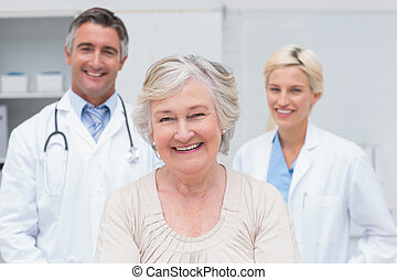 Senior patient smiling with doctors