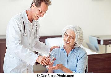 Senior patient taking pills