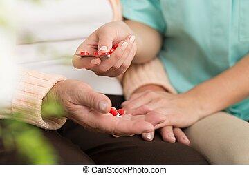 Senior patient taking pills - Close-up of senior patient...