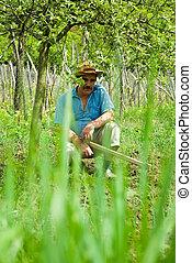 Senior peasant taking a break from digging