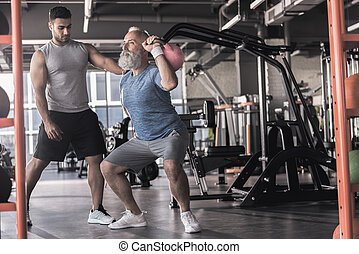 Senior pensioner is having workout with instructor in sport center