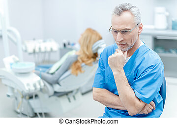 senior pensive dentist in uniform in dental clinic with patient behind