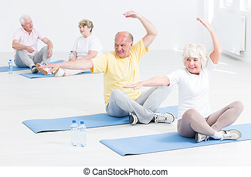 Senior people doing yoga exercises