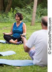 Senior people during yoga class in a park