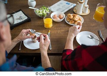 Senior people eating breakfast together