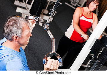 senior people exercising in gym - Senior people in a gym...