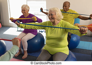 Senior people exercising with resistance band in fitness studio