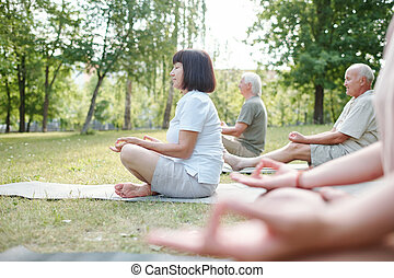 Senior people meditating at yoga practice - Group of ...