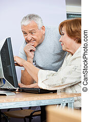 Senior People Using Computer In Class
