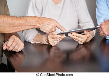 Senior People Using Tablet PC In Computer Class