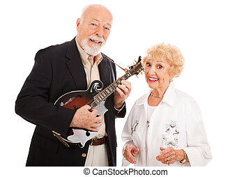 Musical senior couple. He plays mandolin and she sings along. Isolated on white.