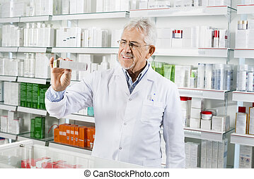 Senior Pharmacist Showing Medicine Box At Counter