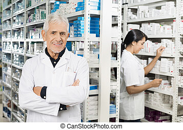 Senior Pharmacist Standing Arms Crossed While Colleague Checking