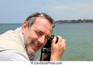 Senior photographer shooting by the sea