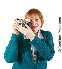 Senior female photographer with analog camera over white background