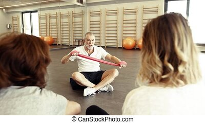 Senior physiotherapist working with female patients. -...