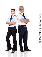 senior pilot and female co-pilot full length portrait on ...