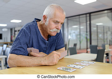 senior playing cards in the retirement house