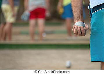 Senior playing petanque, fun and relaxing game. Petanque ball in hand of man