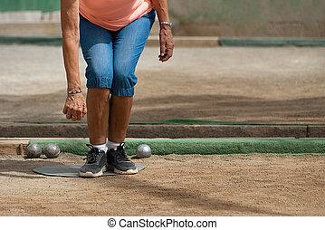 Senior playing petanque