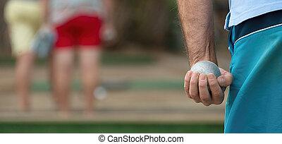 Petanque ball in hand of man - Senior playing petanque,fun...