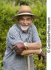 senior posing with a spade in the garden
