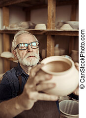 Senior potter in apron and eyeglasses examining ceramic bowl at workshop