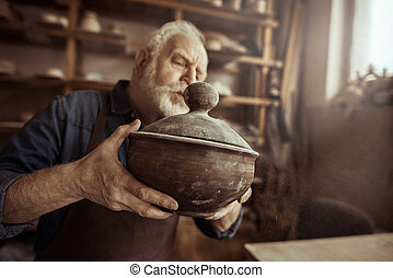 Senior potter in apron examining ceramic bowl at workshop