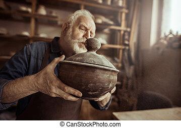 Senior potter in apron examining ceramic bowl at workshop