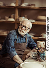 Senior potter in apron sitting at table and daydreaming at workshop