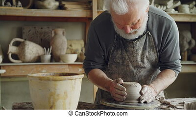 Senior potter is working at bottom part of ceramic pot on...