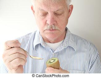 senior prepares to eat kiwifruit