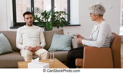 senior psychologist giving water to man patient -...