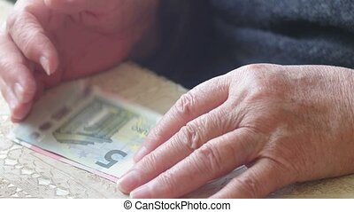 Senior retire woman counting little euro money, toned shot