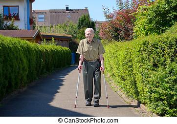 Senior retired man walking on crutches