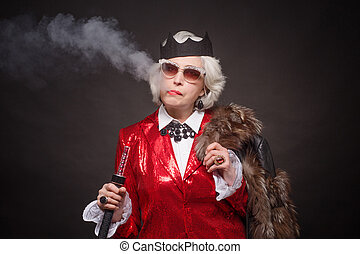 Senior rich woman in red business suit and fur coat smoking ...