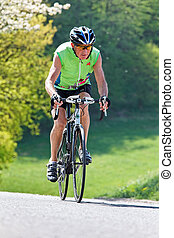 senior riding a bicycle on a road bike