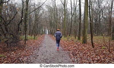 Senior runner on a forest track in the winter