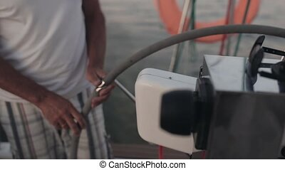 Senior sailor standing behind a steering wheel on the...
