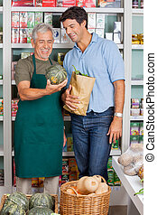 Senior Salesman Assisting Customer In Buying Vegetables