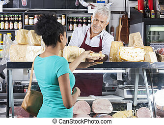 Senior Salesman Selling Cheese To Female Customer